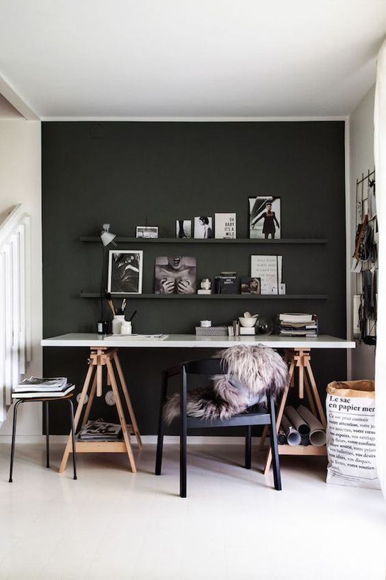 Radni stol sa tamnim pozadinskim zidom
